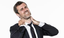 Jeune homme d'affaires barbu souffrant de la tension d'entreprise avec le cou de douleur images libres de droits