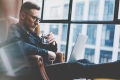 Jeune homme d'affaires barbu travaillant au bureau moderne de grenier Équipez se reposer dans la chaise de vintage, tenant l'eau  photos stock
