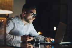 Jeune homme d'affaires barbu travaillant au bureau moderne de grenier la nuit Homme employant le message textuel contemporain de  photographie stock