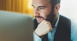 Jeune homme d'affaires barbu travaillant au bureau moderne la nuit Regard de pensée d'homme de conseiller dans l'ordinateur de mo images libres de droits