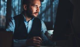 Jeune homme d'affaires barbu travaillant au bureau moderne Regard de pensée d'homme de conseiller dans l'ordinateur de moniteur C photo libre de droits