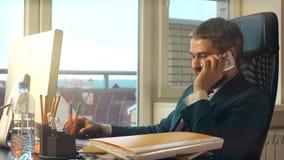 Jeune homme d'affaires barbu travaillant sur son ordinateur, talkink au téléphone portable et ayant le café au bureau tir 4k banque de vidéos