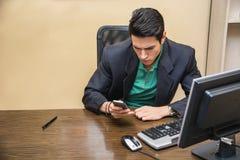Jeune homme d'affaires beau composant sur le téléphone portable ou le texte de dactylographie photos libres de droits