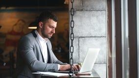Jeune homme d'affaires beau détendant au café pendant le petit déjeuner, dactylographiant sur l'ordinateur portable générique tou banque de vidéos