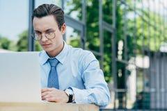 jeune homme d'affaires beau dans des lunettes utilisant l'ordinateur portable en dehors de moderne photos stock