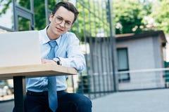 jeune homme d'affaires beau dans des lunettes utilisant le moment d'ordinateur portable images libres de droits