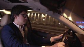 Jeune homme d'affaires beau en verres conduisant une voiture dans une ville de nuit banque de vidéos