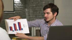 Jeune homme d'affaires beau montrant des diagrammes à son collègue banque de vidéos
