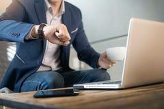 Jeune homme d'affaires beau travaillant à l'ordinateur portable avec la tasse de café Photographie stock libre de droits