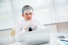 Jeune homme d'affaires beau travaillant à l'ordinateur portable dans le bureau Photos stock