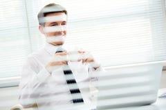Jeune homme d'affaires beau travaillant à l'ordinateur portable dans le bureau Photo libre de droits