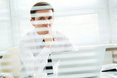 Jeune homme d'affaires beau travaillant à l'ordinateur portable dans le bureau Photographie stock