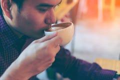 Jeune homme d'affaires bel asiatique souriant tout en lisant sa table Photo stock