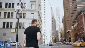 Jeune homme d'affaires bel avec des documents marchant par le secteur financier, route de croisement à New York Mouvement lent banque de vidéos