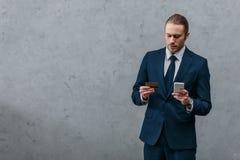 jeune homme d'affaires bel avec la carte de crédit et le smartphone Photo stock