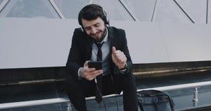 Jeune homme d'affaires bel dans une musique de écoute de costume devant le centre d'affaires utilisant son téléphone clips vidéos