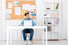 Jeune homme d'affaires bel heureux utilisant l'ordinateur portable dans le bureau Photos libres de droits