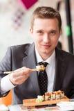 Jeune homme d'affaires bel mangeant des sushi avec des bâtons Images stock