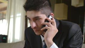Jeune homme d'affaires bel parlant au téléphone intelligent banque de vidéos