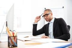 Jeune homme d'affaires bel pensant au travail Photographie stock libre de droits