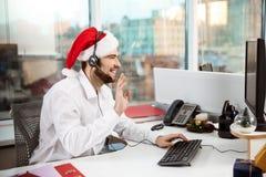 Jeune homme d'affaires bel travaillant dans le bureau le jour de Noël Images stock
