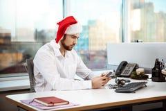 Jeune homme d'affaires bel travaillant dans le bureau le jour de Noël Images libres de droits