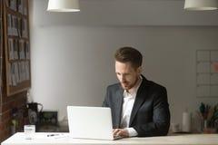 Jeune homme d'affaires bel travaillant sur l'ordinateur portable dans le bureau moderne Photo libre de droits