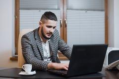 Jeune homme d'affaires bel travaillant sur l'ordinateur portable pendant la pause-café au bureau photo libre de droits