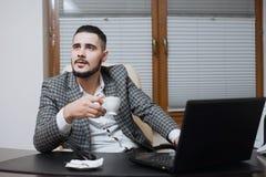 Jeune homme d'affaires bel travaillant sur l'ordinateur portable pendant la pause-café au bureau images libres de droits