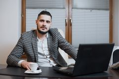 Jeune homme d'affaires bel travaillant sur l'ordinateur portable pendant la pause-café au bureau photo stock