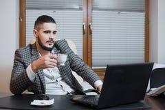 Jeune homme d'affaires bel travaillant sur l'ordinateur portable pendant la pause-café au bureau photographie stock libre de droits