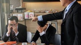 Jeune homme d'affaires blâmé et soumis à une contrainte par le patron Photographie stock