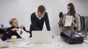 Jeune homme d'affaires, busineswoman adulte et jeune employé travaillant sur le projet à côté de l'ordinateur portable dans une s banque de vidéos