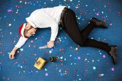 Jeune homme d'affaires célébrant Noël dans le bureau dormant sur le plancher Photographie stock