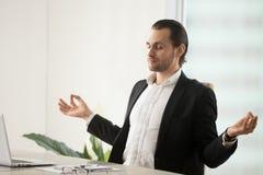 Jeune homme d'affaires calme méditant sur le lieu de travail dans le bureau moderne Photographie stock libre de droits