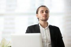 Jeune homme d'affaires calme se reposant sur le lieu de travail avec des yeux fermés Photo libre de droits