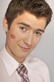 Jeune homme d'affaires caucasien avec la marque de baiser de rouge à lèvres sur sa joue Images stock