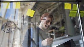 Jeune homme d'affaires caucasien dans les vêtements décontractés utilisant le conseil de verre avec le diagramme tandis que calcu banque de vidéos