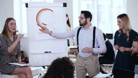 Jeune homme d'affaires caucasien heureux présentant un exposé au flipchart de ventes, discussion active d'équipe lors de séminair banque de vidéos