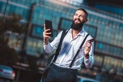 Jeune homme d'affaires caucasien jugeant un comprimé et une carte de crédit extérieurs photos libres de droits