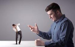 Jeune homme d'affaires combattant avec l'homme d'affaires miniature photos stock