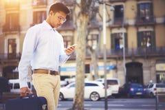 Jeune homme d'affaires concentré avec la marche de lecture d'actualités financières de serviette Photo libre de droits
