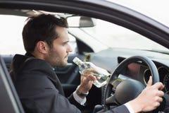Jeune homme d'affaires conduisant tandis qu'ivre Image stock