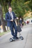 Jeune homme d'affaires conduisant un pédale-scooter Images libres de droits