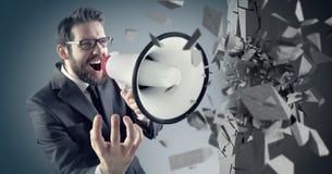 Jeune homme d'affaires écrasant le mur en béton avec un mégaphone Photographie stock
