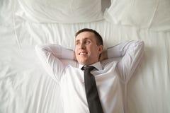 Jeune homme d'affaires détendant dans le lit images stock