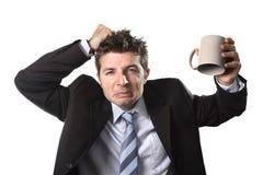 Jeune homme d'affaires d'intoxiqué dans le costume et lien jugeant la tasse de café vide soucieuse image libre de droits