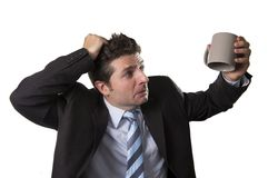 Jeune homme d'affaires d'intoxiqué dans le costume et lien jugeant la tasse de café vide soucieuse Photographie stock