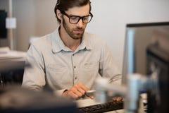 Jeune homme d'affaires dactylographiant sur le clavier d'ordinateur dans le bureau image libre de droits