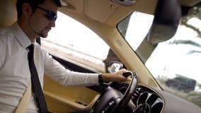 Jeune homme d'affaires dans des lunettes de soleil conduisant la voiture fraîche, service de transport d'élite Photographie stock